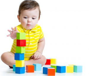 interested infant playing with building blocks